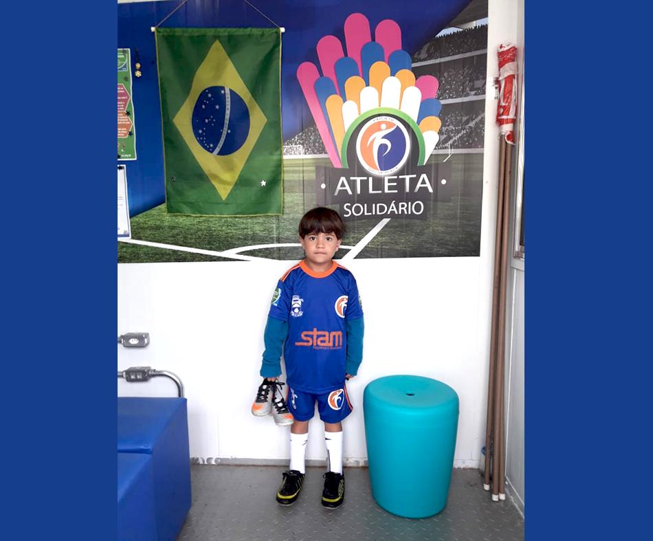 O atleta Guilherme Boêta Pereira - Sub 7, recebe chuteira doada pelo Programa Atleta Solidário.