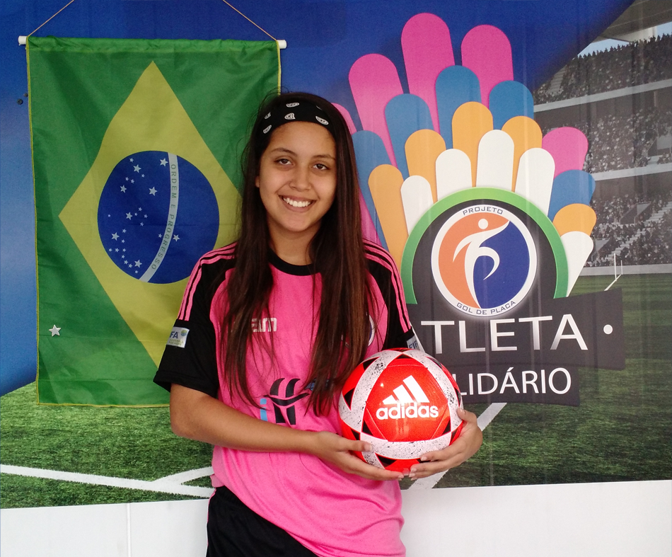 A atleta Yasmim Motta - Sub 15, doa bola para o Programa Atleta Solidário.