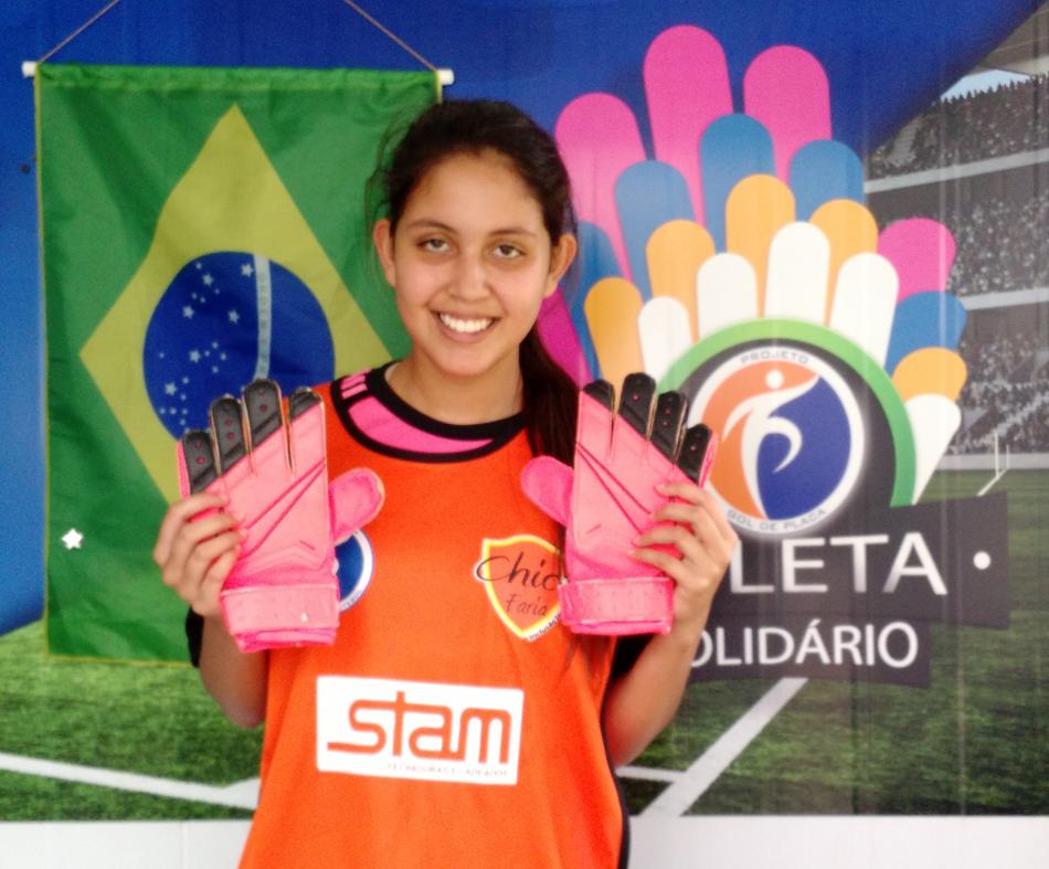 A atleta Yasmim Motta - Sub 15, doa luvas para o Programa Atleta Solidário.