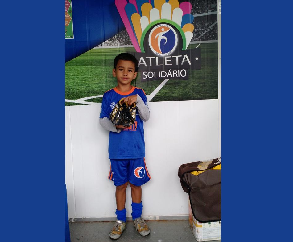 O atleta Bernardo Estevam de Souza recebe chuteira doada pela atleta Karolayne.