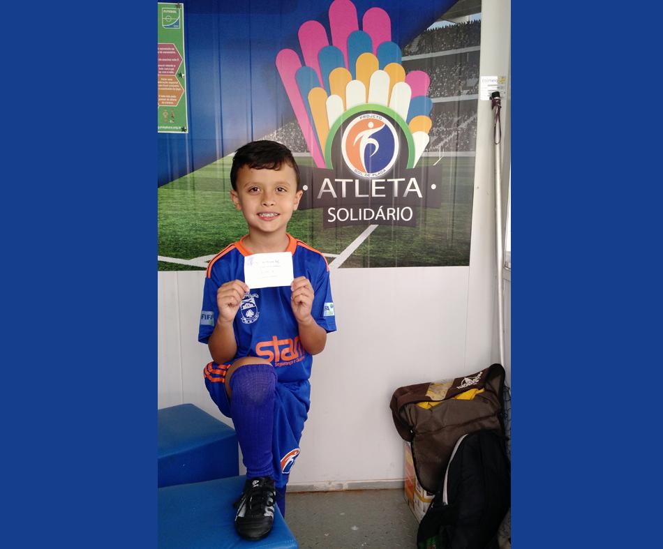 O atleta Heitor Rocha Pinheiro Hotzz recebe chuteira doada pelo atleta José Gabriel.